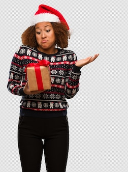 Young black woman holding a gift in christmas day doubting and shrugging shoulders
