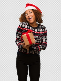Young black woman holding a gift in christmas day dreaming of achieving goals and purposes
