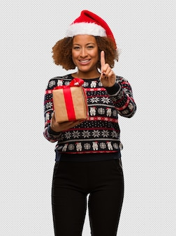 Young black woman holding a gift in christmas day showing number one