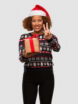 Young black woman holding a gift in christmas day showing number two