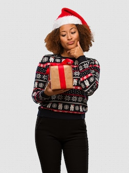 Young black woman holding a gift in christmas day thinking about an idea