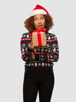 Young black woman holding a gift in christmas day tired and bored