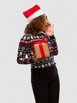 Young black woman holding a gift in christmas day whispering gossip undertone