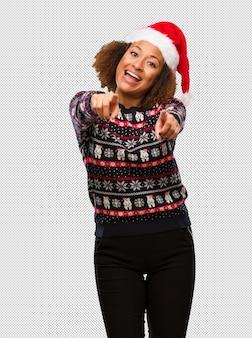 인쇄 명랑하고 웃는 트렌디 한 크리스마스 스웨터에 젊은 흑인 여성