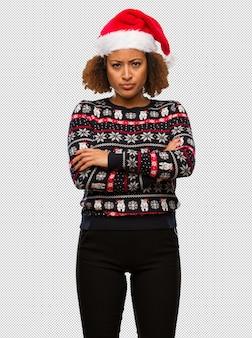 인쇄 교차 무기와 트렌디 한 크리스마스 스웨터에 젊은 흑인 여성 편안한