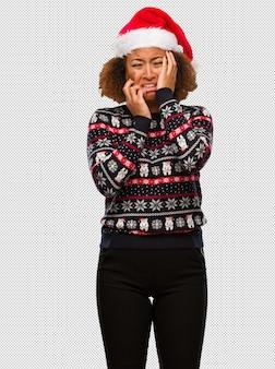 トレンディなクリスマスのセーターで、欲求不満で悲しい印象の若い黒人女性
