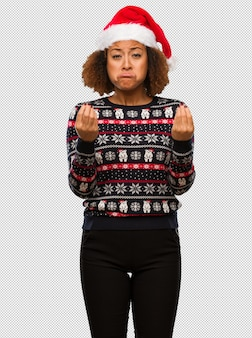 인쇄 요구의 제스처를 하 고 트렌디 한 크리스마스 스웨터에 젊은 흑인 여성