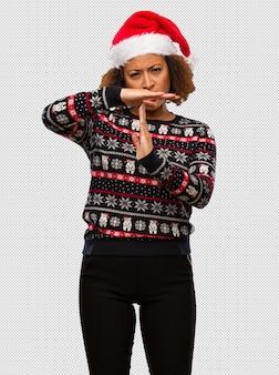 인쇄 시간 제한 제스처를 하 고 유행 크리스마스 스웨터에 젊은 흑인 여성