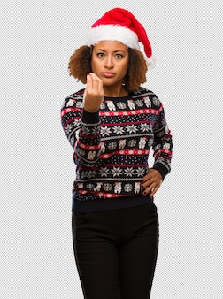 전형적인 이탈리아 제스처를 하 고 인쇄 유행 크리스마스 스웨터에 젊은 흑인 여성