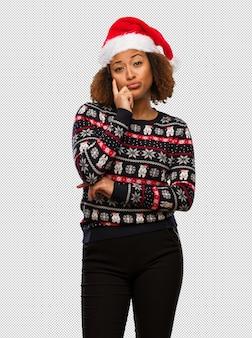 인쇄 의심과 혼란 유행 크리스마스 스웨터에 젊은 흑인 여성