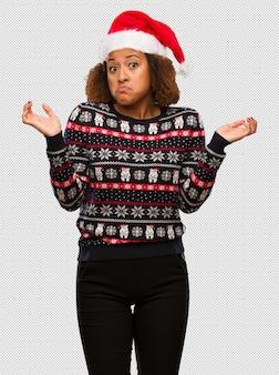 인쇄 의심과 어깨를 shrugging 유행 크리스마스 스웨터에 젊은 흑인 여성