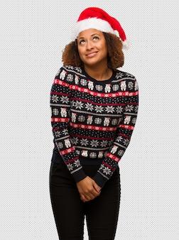 Молодая чернокожая женщина в модном рождественском свитере с принтом, мечтающим о достижении целей и задач