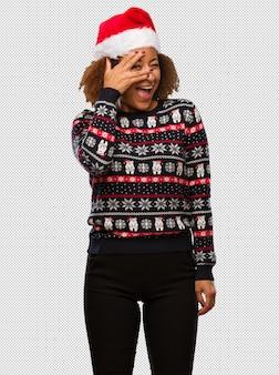 인쇄와 함께 최신 유행 크리스마스 스웨터에 젊은 흑인 여성 당황과 동시에 웃고