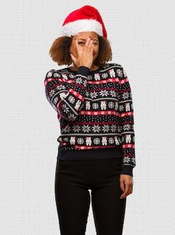 인쇄 유행 크리스마스 스웨터에 젊은 흑인 여성이 걱정과 무서워 느낌