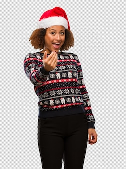 인쇄 초대와 트렌디 한 크리스마스 스웨터에 젊은 흑인 여성
