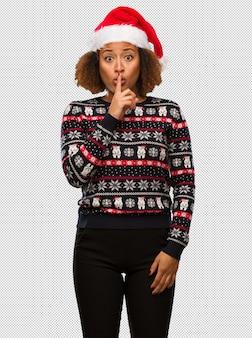 流行のクリスマスのセーターで、秘密を守ったり、沈黙を求める印刷物で、若い黒人の女性