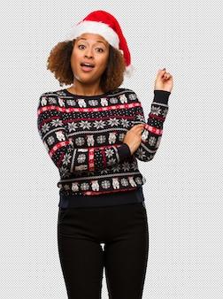 인쇄 손가락으로 측면을 가리키는 유행 크리스마스 스웨터에 젊은 흑인 여성