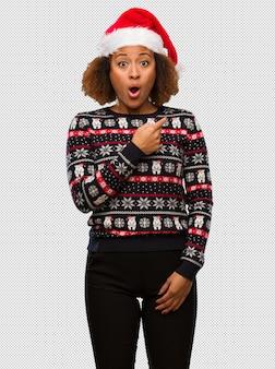 인쇄 측면을 가리키는 유행 크리스마스 스웨터에 젊은 흑인 여성