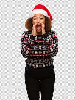 인쇄 앞에 뭔가 행복 소리와 유행 크리스마스 스웨터에 젊은 흑인 여성