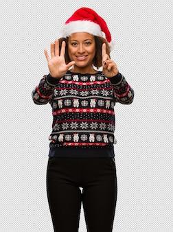 トレンディなクリスマスのセーターで若い黒人の女性が6番