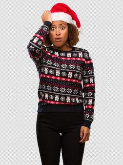 인쇄 걱정과 압도 유행 크리스마스 스웨터에 젊은 흑인 여성