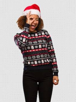 Young black woman in a trendy christmas sweater with print confident doing ok gesture on eye