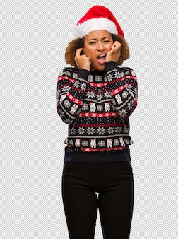 Young black woman in a trendy christmas sweater with print covering ears with hands
