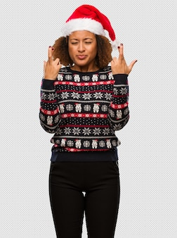 Young black woman in a trendy christmas sweater with print crossing fingers for having luck