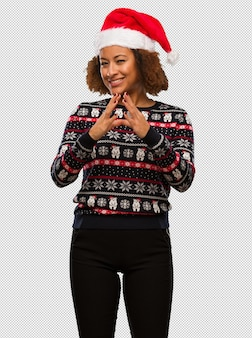 Young black woman in a trendy christmas sweater with print devising a plan