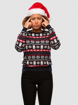 Young black woman in a trendy christmas sweater with print doing a concentration gesture