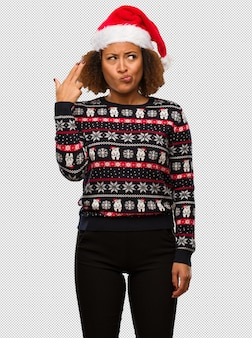 Young black woman in a trendy christmas sweater with print doing a suicide gesture