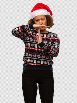 Young black woman in a trendy christmas sweater with print doing a timeout gesture