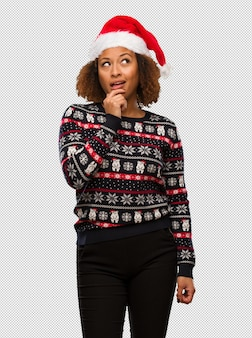 Young black woman in a trendy christmas sweater with print doubting and confused