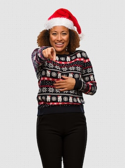 Young black woman in a trendy christmas sweater with print dreams of achieving goals and purposes