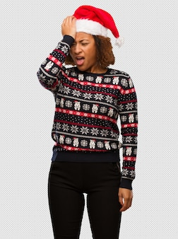 Young black woman in a trendy christmas sweater with print forgetful, realize something