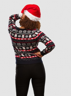 Young black woman in a trendy christmas sweater with print from behind thinking about something