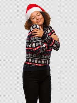 Young black woman in a trendy christmas sweater with print giving a hug