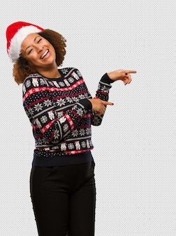Young black woman in a trendy christmas sweater with print pointing to the side with finger