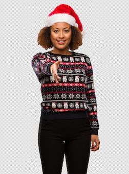 Young black woman in a trendy christmas sweater with print reaching out to greet someone