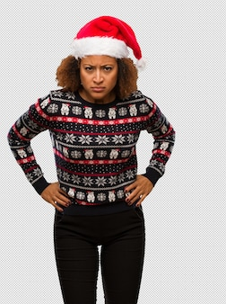 Young black woman in a trendy christmas sweater with print scolding someone very angry