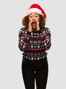 Young black woman in a trendy christmas sweater with print shouting something happy to the front