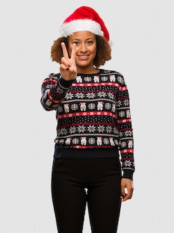 Young black woman in a trendy christmas sweater with print showing number two