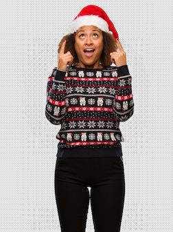 Young black woman in a trendy christmas sweater with print surprised pointing up to show something