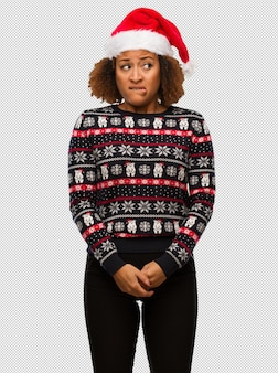 Young black woman in a trendy christmas sweater with print thinking about an idea