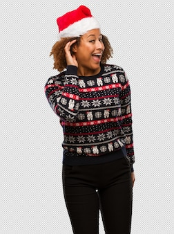 Young black woman in a trendy christmas sweater with print try to listening a gossip