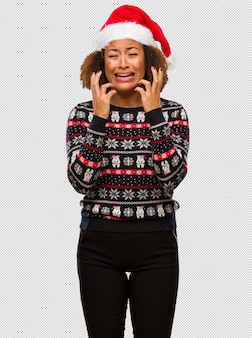 Young black woman in a trendy christmas sweater with print very scared and afraid