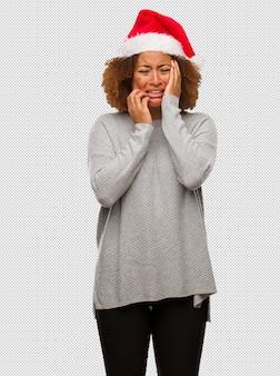 絶望的で悲しいサンタの帽子を身に着けている若い黒人の女性