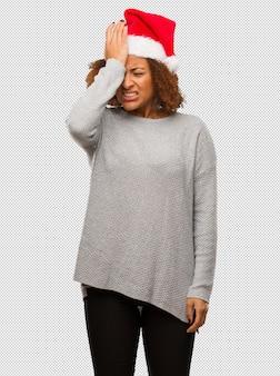 잊을 수없는 산타 모자를 쓰고 젊은 흑인 여성, 뭔가 실현