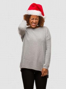 首の痛みを患っているサンタの帽子を着ている若い黒人の女性