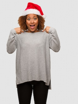Молодая чернокожая женщина в шляпе санта удивлена, чувствует себя успешной и процветающей